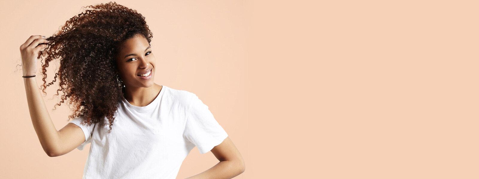 femme aux cheveux noirs bouclés vêtue d'un t-shirt blanc