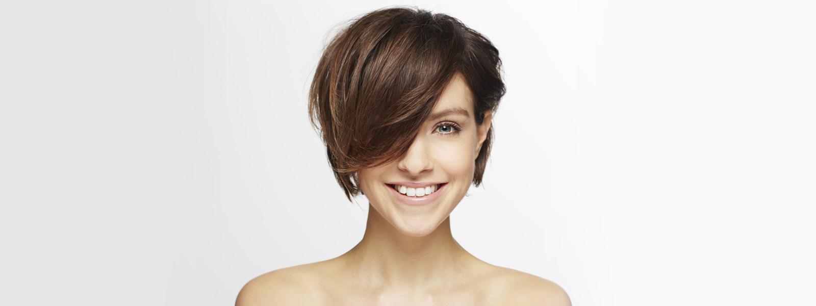 femme aux cheveux courts bruns avec une frange qui sourit