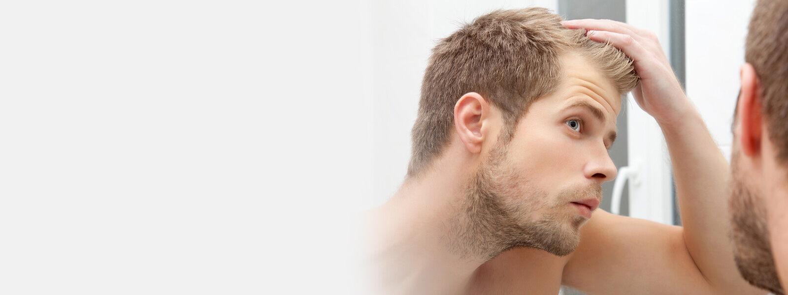 homme aux cheveux châtains qui se regarde dans un miroir