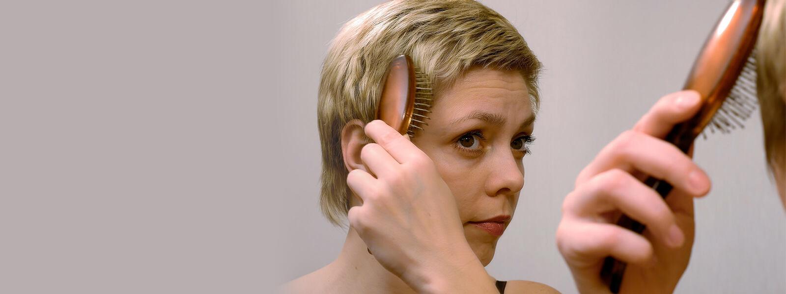 femme aux cheveux courts qui se brosse les cheveux amincis