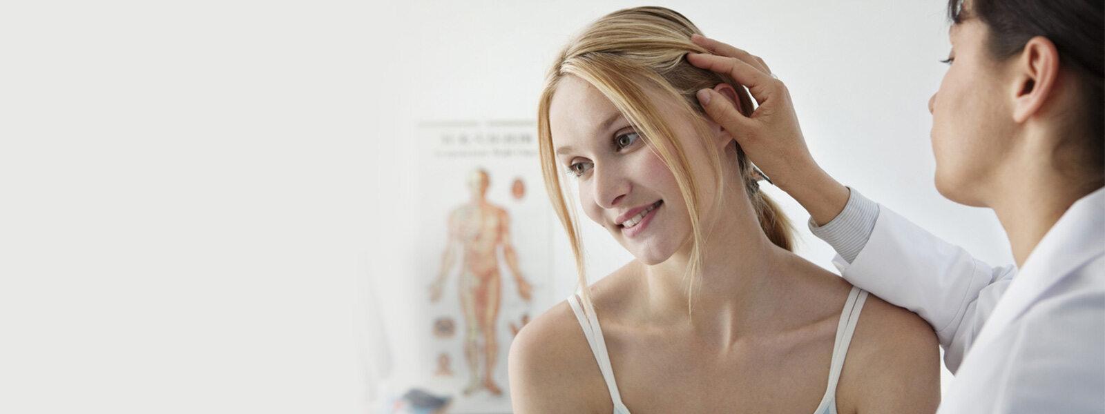 médecin inspectant la perte de cheveux d'une femme