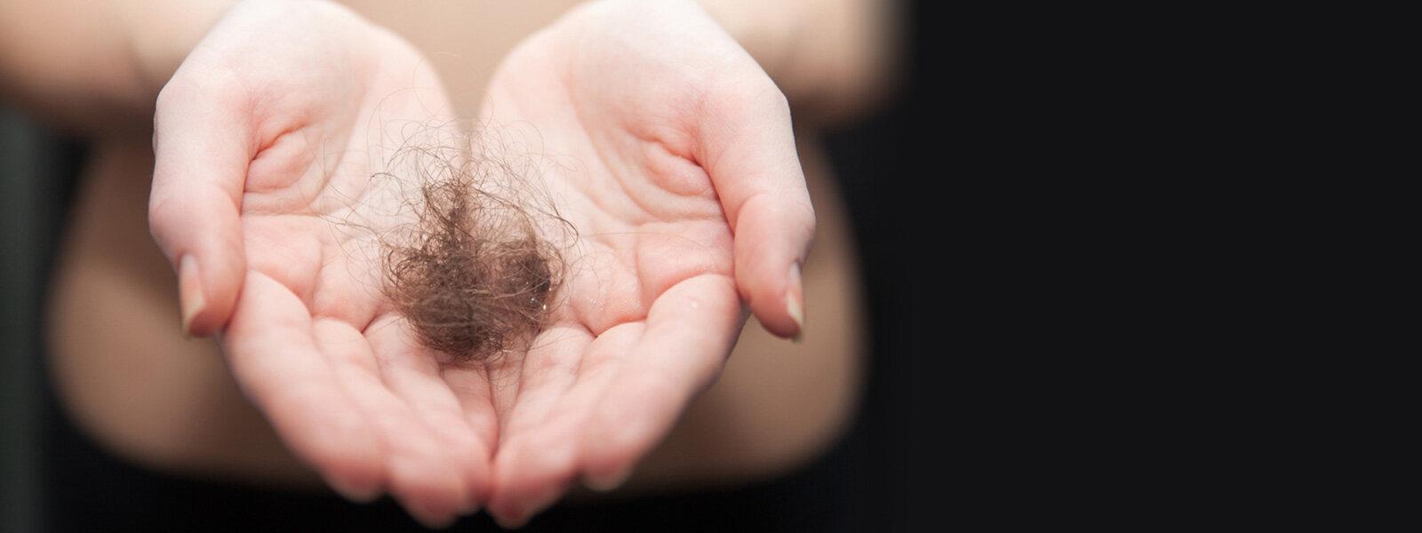 femme tenant dans ses mains un touffe de cheveux