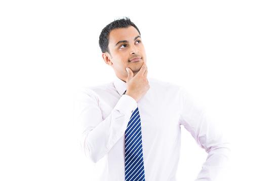 homme vêtu d'une chemise et d'une cravate qui pense à la repousse des cheveux