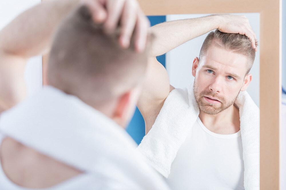 homme appliquant le traitement ROGAINE® pour la repousse des cheveux