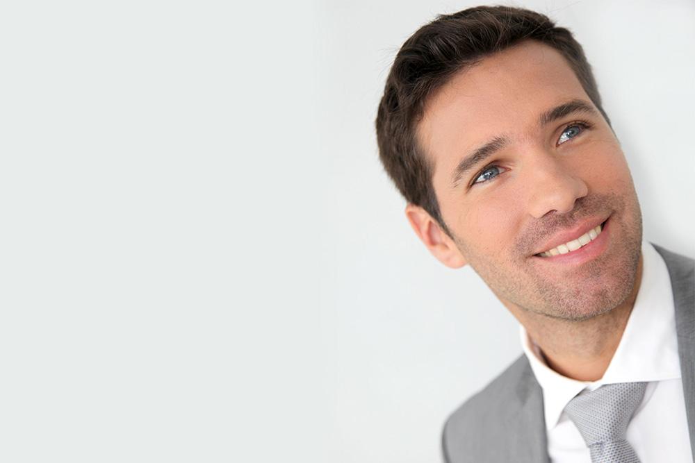 homme aux cheveux foncés et vêtu d'un complet gris qui sourit