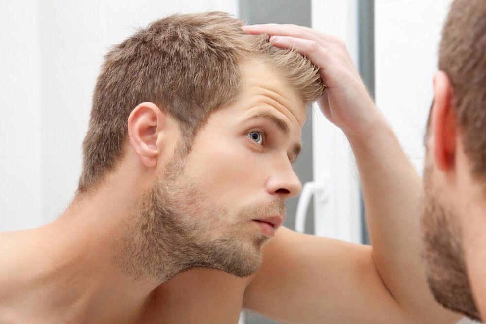 homme regardant ses cheveux dans un miroir