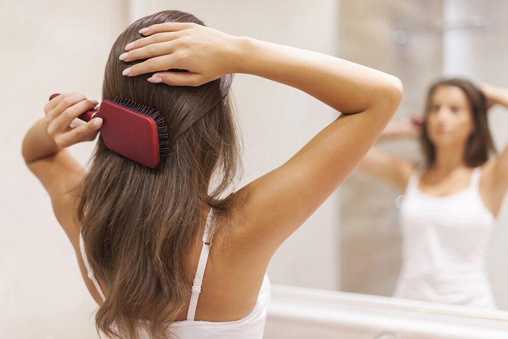 femme brunette se brossant les cheveux