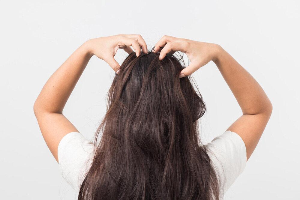 femme brunette qui se masse le cuir chevelu pour la repousse des cheveux