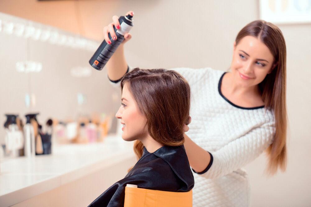 coiffeuse appliquant un fixatif sur les cheveux de sa cliente