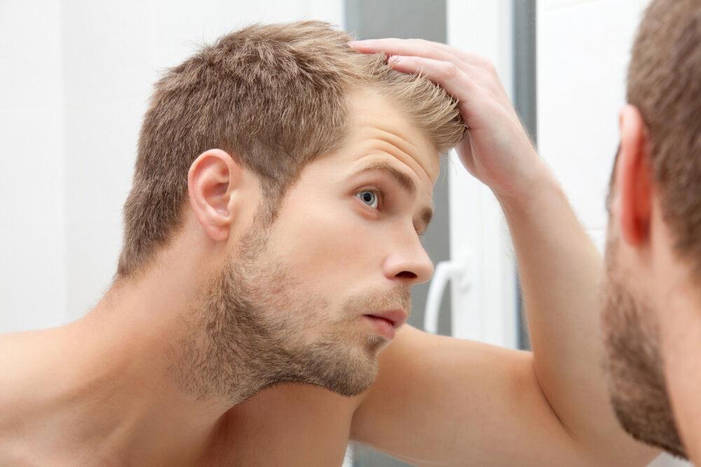 jeune homme qui regarde ses tempes dans un miroir