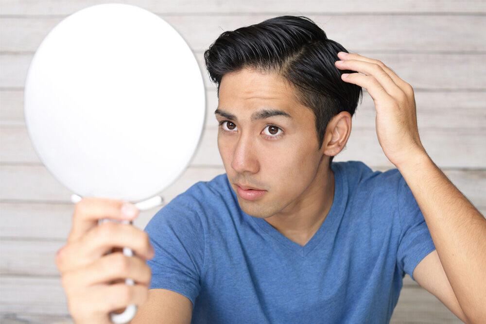 homme tenant un miroir et se regardant les cheveux