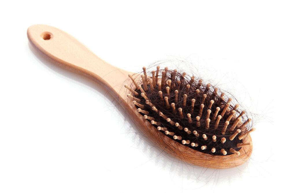 touffe de cheveux sur une brosse à cheveux en bois