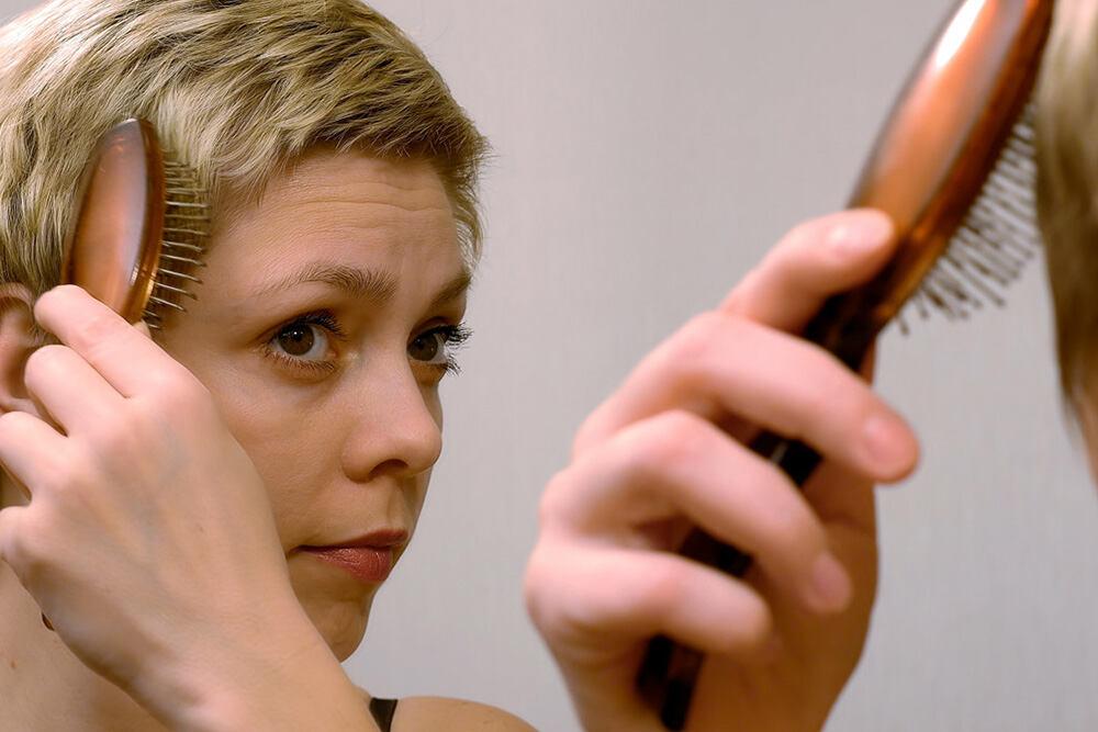 femme blonde se brossant les cheveux qui sont courts