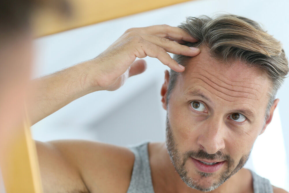 man looking at his hair growth in the mirror